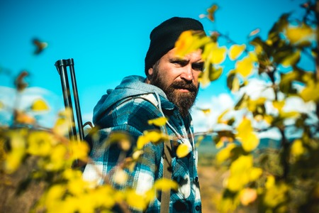 Bearded hunter man holding gun and walking in forest. Hunting without borders. Hunter with shotgun gun on hunt.
