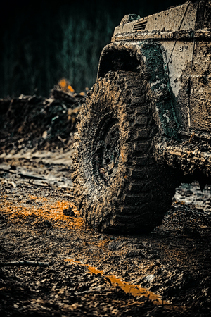 Off road sport truck between mountains landscape. Mudding is off-roading through an area of wet mud or clay. Bottom view to big offroad car wheel on country road and mountains backdrop. 스톡 콘텐츠