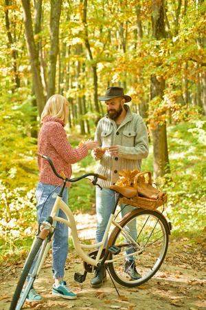 Pareja con bicicleta vintage. Pareja de otoño está montando la bicicleta en el parque. Gente activa. Al aire libre. Otoño mujer un hombre barbudo con bicicleta retro en el parque otoñal