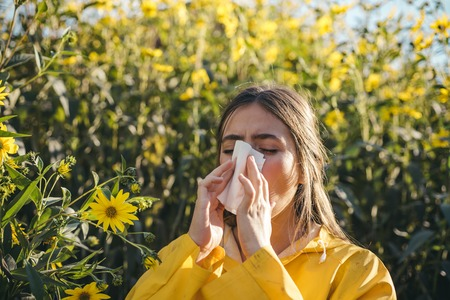 Cold flu season, runny nose. Flowering trees in background. Young girl sneezing and holding paper tissue in one hand and flower bouquet in other. Flu. Allergy season. 写真素材