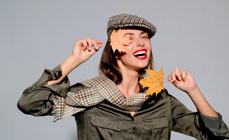 Autumn mood and the weather are warm and sunny and rain is possible. Surprise woman playing with leaves and looking at camera. Attractive young woman in a seasonal clothes with golden leaf. Фото со стока