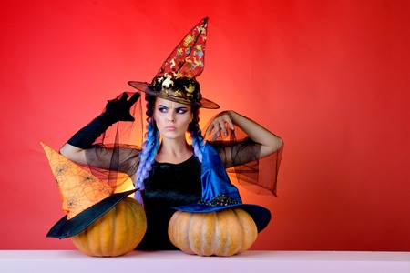Beautiful young woman in black witch costume with hat standing over red background. Happy young woman in witch halloween costume on party over isolated background. Best ideas for Halloween.