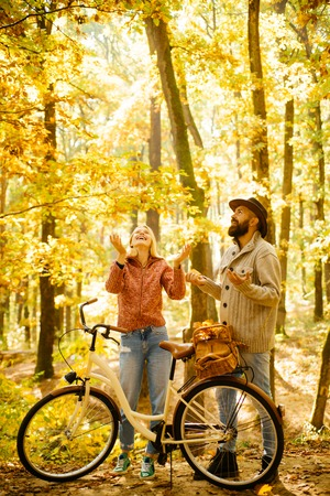 Autumn couple is riding the bicycle in the park. Active people. Outdoors. Autumn woman an bearded man with retro bike in autumnal park. Couple with vintage bike.