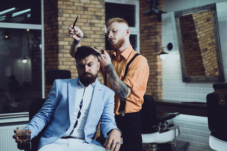 Hair Preparation is just for dashing chap. Bearded stylish barber shop client. Bearded client visiting barber shop. Barber scissors. Beard styling and cut. Making haircut look perfect in barber shop. Stock Photo