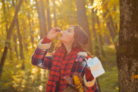 Young woman with nose wiper near autumn tree. Portrait Of Young Woman Sniffing Nasal Spray Closing One Nostril. Woman with allergy symptoms blowing nose.