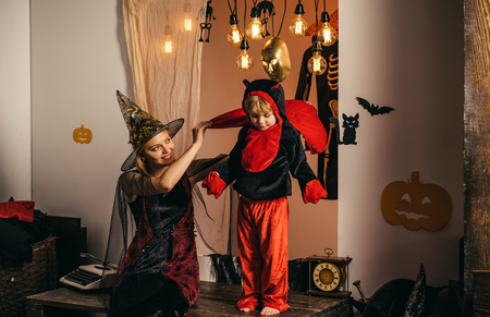 Mom and son play for all saints day in witchs costume at home. Mother and child boy playing together. 31 october. Magic hat. Best ideas for Halloween. Mother wearing as witch, son wearing as devil. Stok Fotoğraf