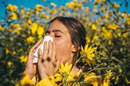 Young girl sneezing and holding paper tissue in one hand and flower bouquet in other. Young woman got nose allergy, flu sneezing nose. Young woman is going to sneeze. Flu. Closeup portrait.