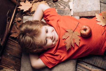 Kid having fun with Leaf fall. Smiling little boy wearing in fashionable seasonal clothes having Autumnal mood. Kid playing in autumn. Cute little child boy are getting ready for autumn.