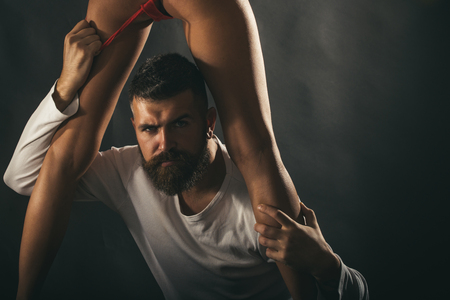 Sexy closeup portrait of handsome brutal bearded male model with beautiful woman legs. Sensual coule and point orgasm. Brutal man takes off her lingerie. Sexy and sensual copy space. Banque d'images