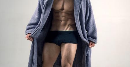 Modello maschile in topless con bel busto. Gay in biancheria intima e accappatoio da uomo. Corpo e busto sexy. Concetto di biancheria intima.