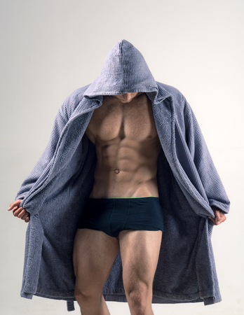 Muscular male model in underwear. Gay man in the morning after training. Spotlife and healthy concept. Man underwear and bathrobe. Muscular man concept. 스톡 콘텐츠