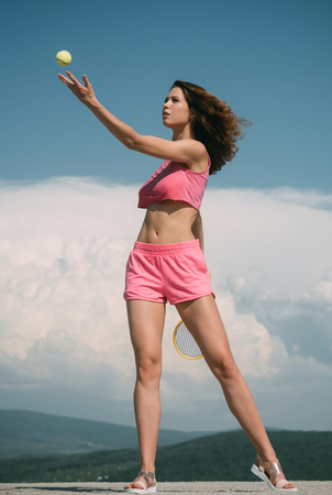 Sporty girl play tennis in pink tracksuit. Woman serving the ball for a game of tennis on court. Sport lifestyle and healthy concept. Training in the tennis on court. Female sport and workout. Banque d'images