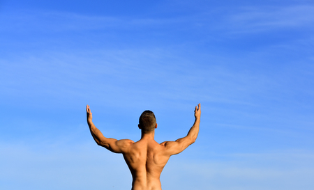 Sport copy space. Healthy men in blue sky background. Perfect big power tanned body posing with beautiful back against blank copy space wall for your advertising content. Freedom and enjoying nature.