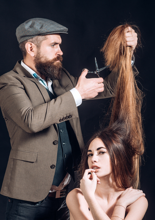 Bearded Hairdresser make fashion hairstail. Beautiful model with very long hair. Hairdresser, beauty salon.