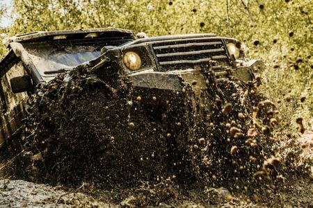 El lodo consiste en desplazarse fuera de la carretera a través de un área de lodo húmedo o arcilla. Pista sobre barro. Mueva las ruedas y los neumáticos todoterreno que va por el polvo.