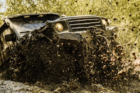 Mudding is off-roading through an area of wet mud or clay. Track on mud. Motion the wheels tires and off-road that goes in the dust. Stock Photo