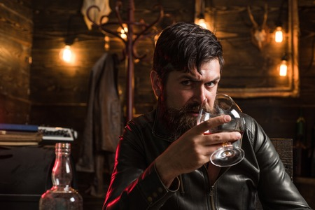 Bearded man drinking alcohol. Whisky, brandy or cognac concept. Serious sad man having alcohol addiction. Alcohol addiction concept.