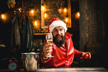 Santa congratulation you with Merry christmas and happy new year. Man in Santa Claus hat and champagne. Winter traditions.
