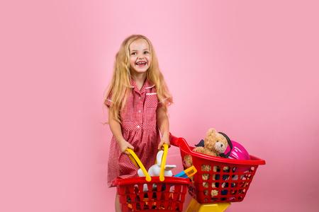 La nueva línea retro. Pequeño adicto a las compras con carrito de compras. Compras felices de la niña. Pequeña niña feliz sonriendo en la tienda. Pequeño comprador. Ir de compras es un poco de terapia
