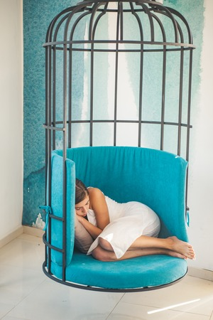 woman relax in cage chair at home. daytime sleep of tired girl in cage chair. sweet and comfort dream, morning. modern furniture design and home comfort. woman sleep in iron cage. time to relax.