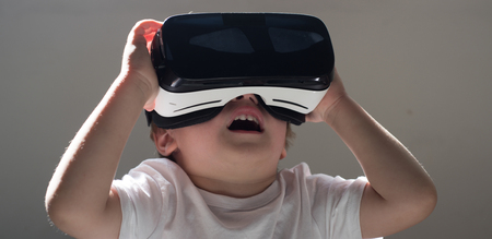 Enjoying new technology. Little child in VR headset. Small child wear wireless VR glasses. Using future technology. The future