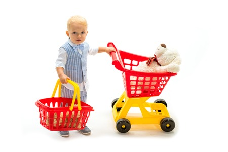 savings on purchases. little boy go shopping with full cart. happy childhood and care. shopping for children. little boy child in toy shop. Excitement. Pleasant price. How about price. Shopping alone Stock Photo