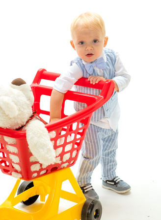 happy childhood and care. shopping for children. little boy child in toy shop. little boy go shopping with full cart. savings on purchases. New arrivals. Real happiness. Friendly shop assistant