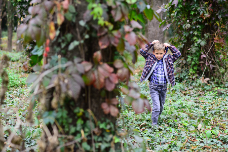Lets just go walking. Little boy walking around in woods. Little boy walking into the wild. Enjoying the scenery and the wildlife Фото со стока