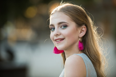 summer fashion woman. Pretty girl with fashionable hair and pink earrings. Beautiful female. Beauty and fashion look of model. Perfect female. happy woman with stylish makeup and long blonde hair