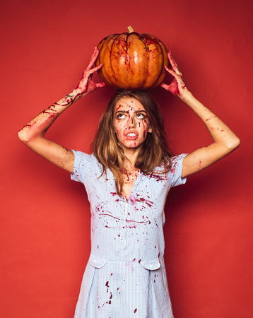 Beautiful Young woman as sexy vampire in blue dress - halloween concept. Beautiful young surprised woman in costume holding pumpkin. Woman Possessed as a zombie or demon. 版權商用圖片