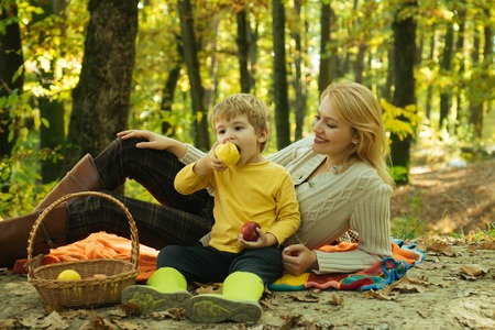 Autumn Family Camping in the Park and eating apple. Active people and happy family concept. Outdoors. Autumn camping with kids and mother. Good family concept.