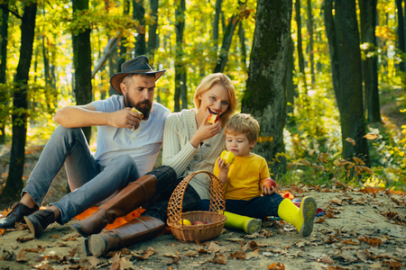 Autumn Family Camping in the Park and eating apple. Active people and happy family concept. Outdoors. Autumn camping with kids and parents. Happy family concept. Stock Photo