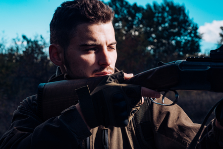 Close up snipers carbine at the outdoor hunting. Close up Portrait of hamdsome Hunter. Hunter with shotgun gun on hunt. Stock Photo