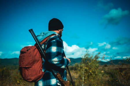 Illegal Hunting Poacher in the Forest. Hunter with shotgun gun on hunt. American hunting rifles. Gun rifle. Stock Photo