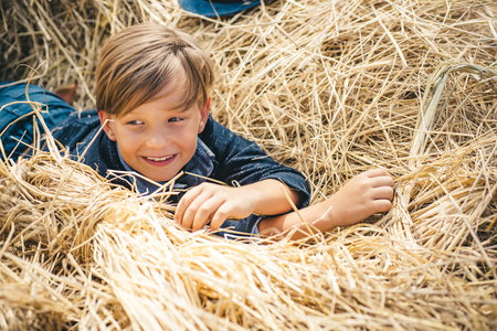 Portrait of a cheerful boy lying in a hay. Happy child at the autumn fair. Little boy advertises natural products. The boy advertises childrens clothes for the autumn.