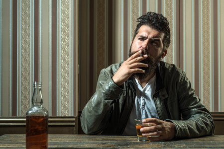 Man drinks brandy or whiskey. Bearded man wearing suit and drinking whiskey brandy or cognac. Sommelier tastes alcohol drink. Drinking and party concept. Degustation and tasting.