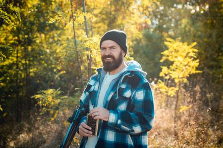 Hunter with shotgun gun on hunt. Bearded hunter man holding gun and walking in forest.