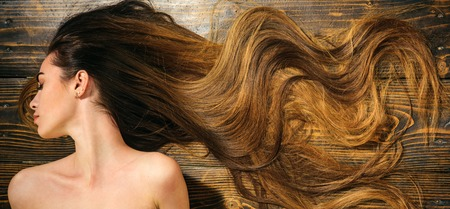 Capelli molto lunghi su fondo in legno. Bellissimo modello con acconciatura riccia. Concetto di parrucchiere. Prodotti per la cura e i capelli.