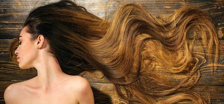 Sehr langes Haar auf hölzernem Hintergrund. Schönes Modell mit lockiger Frisur. Friseursalon Konzept. Pflege- und Haarprodukte.