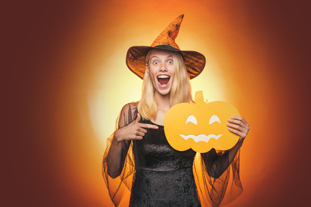 Beautiful surprised woman in witches hat and costume - showing products. Halloween Woman portrait. Beauty Woman posing with Pumpkin and Halloween hat. Helloween people concept.