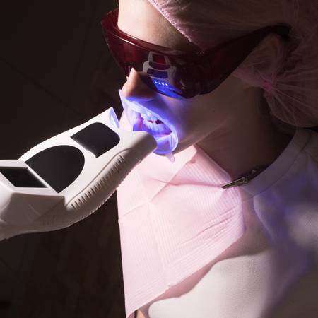 Patient visiting dentist for teeth whitening in clinic. Woman showing her perfect straight white teeth. Stock Photo