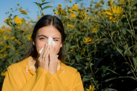 Beautiful sexy young woman lies on flowers background. Young woman got nose allergy, flu sneezing nose. Pretty woman got flu sneezing nose. Flu.