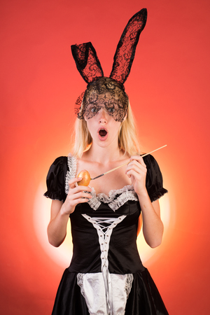 Happy young woman wearing bunny ears and having Easter Eggs copy space. Crazy people. Woman easter. Beautiful sensual blonde.
