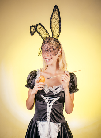 Sweet young woman painting eggs, copy space. Crazy people. Easter eggs. A beautiful sensual blonde depicts an Easter egg on a bright yellow background. Stock Photo