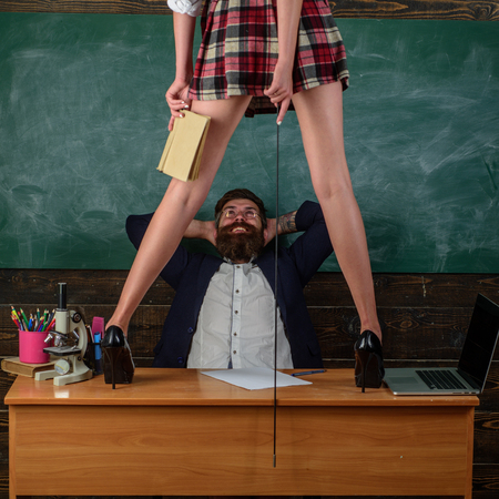 First Sexual Experience. Human Sexuality Lesson Plans. Bearded teacher looks at sexy female students. Erotic education and sex Symbols on chalkboard. Zdjęcie Seryjne