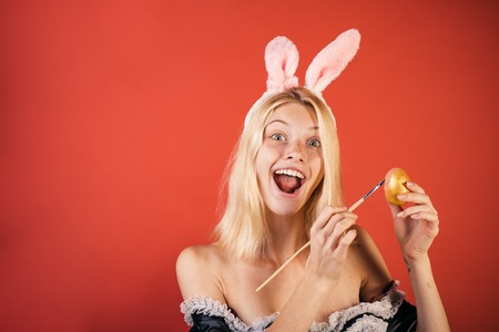 Happy young woman in a rabbit costume with Easter eggs. Surprise woman. Happy easter. Fashion portrait of beautiful sensual woman. The concept of preparation for the celebration of Easter