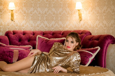 Fashion Model, Elegant Woman in Gold Dress in bed. Beautiful stunning lady in amazing glitter sequins dress sitting on luxury armchair. Bright red full lips, hollywood make up.