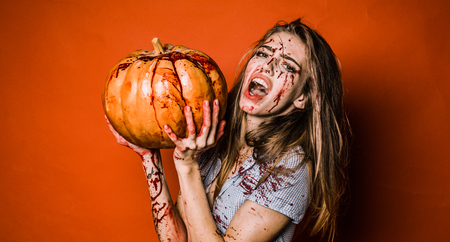 Woman with bloody make up. Halloween sexy girl in blood with pumpkin. Horror photo of sexy girl murderers hold pumpkin in her hand. 版權商用圖片