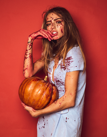 Beautiful bloody woman in costume holding pumpkin. Pretty young blonde woman clothed in dress with pumpkins. Model girl in Halloween costume and make up.