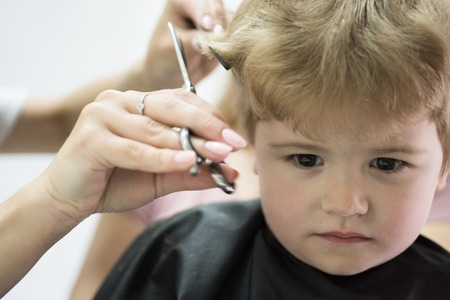 Hair salon that specializes in toddlers. Little boy with blond hair at hairdresser. Small child in hairdressing salon. Cute boys hairstyle. Hair salon for kids. Making haircut look perfect
